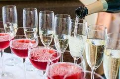 侍酒者倾吐的香槟到玻璃里, 免版税库存图片