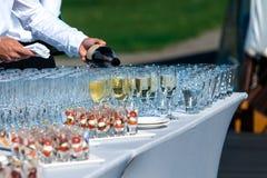 侍酒者倾吐酒精饮料入在宴餐的玻璃 免版税库存照片