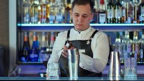 侍酒者做一个鸡尾酒在酒吧,倾吐对从振动器的一块玻璃 免版税库存照片