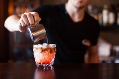 侍酒者做鸡尾酒在酒吧柜台在夜总会,被定调子 免版税图库摄影