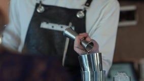 侍酒者做鸡尾酒在酒吧柜台在夜总会 免版税图库摄影