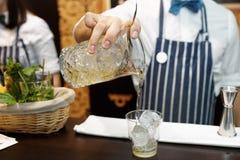 侍酒者做鸡尾酒在酒吧柜台 免版税库存图片