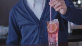 侍酒者在与鸡尾酒的一块玻璃投入秸杆并且传送它给客户 股票视频