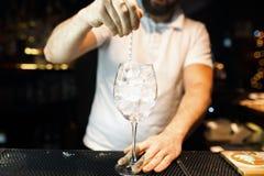 侍酒者在酒吧的白色T恤的或在夜总会和做一个酒精鸡尾酒 生活方式 图库摄影