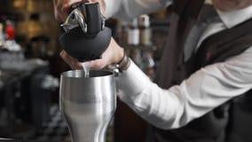侍酒者紧压汁液到鸡尾酒搅拌器,做鸡尾酒,男服务员在工作,在酒吧柜台 股票视频