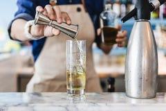 侍酒者轻轻地倾吐在一块玻璃的酒精与做的鸡尾酒冰 库存照片