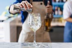 侍酒者轻轻地倾吐酒精和苏打在一个酒杯与冰做的鸡尾酒 免版税库存照片