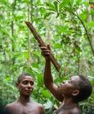 侏儒的妇女在森林里喝从藤本植物的水 库存照片