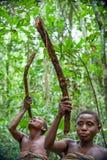 侏儒的妇女在森林里喝从藤本植物的水 免版税库存照片