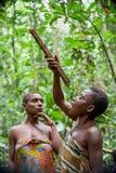 侏儒的妇女在森林里喝从藤本植物的水 图库摄影