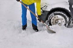 供以人员一辆汽车的清洁轮子在雪的 库存图片