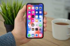 供以人员举行与IOS 11的手iPhone x在屏幕上 免版税图库摄影