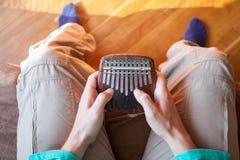 供以人员举行传统非洲乐器kalimba在一个` s手上 使用在kalimba的人 免版税库存图片