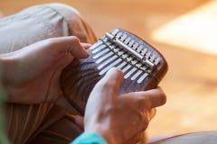 供以人员举行传统非洲乐器kalimba在一个` s手上 供以人员使用在非洲仪器的版本 免版税库存照片