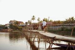 供以人员乘坐在一个木桥的一辆摩托车在地方村庄亚洲人 免版税库存图片