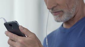 供以人员他在智能手机的喜爱的歌曲,容易接近的app组成的播放表  股票视频