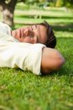 供以人员位于与他的闭上的眼睛和他顶头休息的端 免版税库存图片