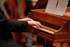 供以人员使用在一架老钢琴的手在古典音乐会 免版税库存照片