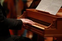 供以人员使用在一架老钢琴的手在古典音乐会 免版税库存图片