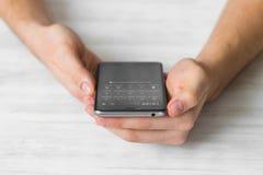 供以人员使用黑智能手机一个触摸屏巧妙的电话在咖啡馆手上紧密,葡萄酒上色 库存图片