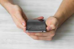 供以人员使用黑智能手机在cafehands的一个触摸屏巧妙的电话紧密,葡萄酒上色 免版税库存图片
