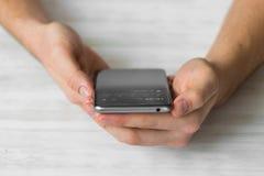 供以人员使用黑智能手机在cafehands的一个触摸屏巧妙的电话紧密,葡萄酒上色 库存照片