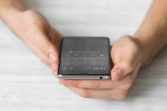 供以人员使用黑智能手机触摸屏巧妙的电话手紧密,葡萄酒上色 库存照片