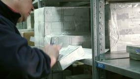 供以人员保管员从汽车零件架子仓库的作为物品并且做标记在纸 影视素材