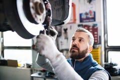 供以人员修理在车库的技工一辆汽车 免版税图库摄影