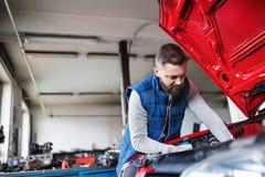供以人员修理在车库的技工一辆汽车 免版税库存图片