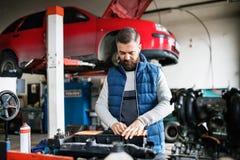 供以人员修理在车库的技工一辆汽车 库存图片
