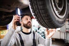 供以人员修理在车库的技工一辆汽车 图库摄影