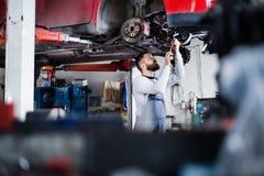 供以人员修理在车库的技工一辆汽车 免版税库存照片