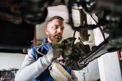供以人员修理在车库的技工一辆汽车 库存照片