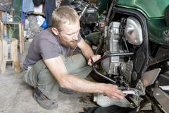 供以人员修理在车库,特写镜头的摩托车 库存图片
