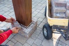 供以人员修造在一个木眺望台的一根砖柱子 库存图片
