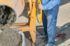 供以人员倾吐的湿水泥入从搅拌器的独轮车 免版税库存图片
