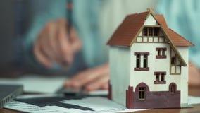 供以人员做住房建造计划,房子模型在桌上的 在家工作的设计师 股票视频