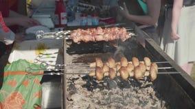 供以人员做猪肉shashlik和蘑菇的` s手在木炭格栅外面 股票视频