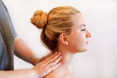 供以人员做脖子按摩在康复中心 库存图片