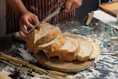 供以人员准备小圆面包在桌上在面包店,洒面粉的人  免版税库存照片