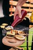 供以人员加番茄酱到在格栅烹调的户外汉堡 库存照片