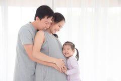 供以人员和他的拥抱怀孕的妻子和微笑的女儿 免版税库存图片