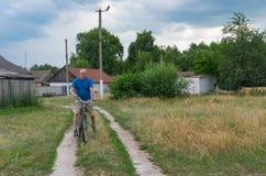 供以人员在一辆古老自行车的骑马在乡下公路 库存图片