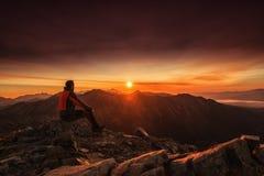 供以人员在上升山的上面的就座在日出,远足和 图库摄影