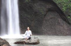 供以人员在凝思瑜伽坐岩石在瀑布Tibumana 库存图片