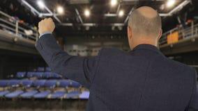 供以人员在大厅后面视图的讲的和运动的握紧拳头在最前面的公众 影视素材