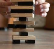 供以人员在家使用与木比赛jenga 教育、风险、发展和成长的概念 图库摄影