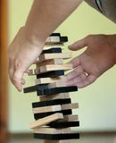供以人员在家使用与木比赛jenga 教育、风险、发展和成长的概念 免版税库存照片