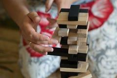 供以人员在家使用与木比赛jenga 教育、风险、发展和成长的概念 免版税库存图片